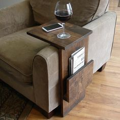 Handcrafted tray table stand with side storage slot. The perfect addition to a sofa chair in any home, apartment, condo, or man cave.  It has been sanded down, then stained and sealed with a dark walnut finish. The stand is free standing and can be used anywhere around the house.  Non-marking, non-skid rubber pads are installed on the bottom of base of the stand. This piece does not include the accessory items as shown in the pictures.  The color of the stained wood captured in the photos…