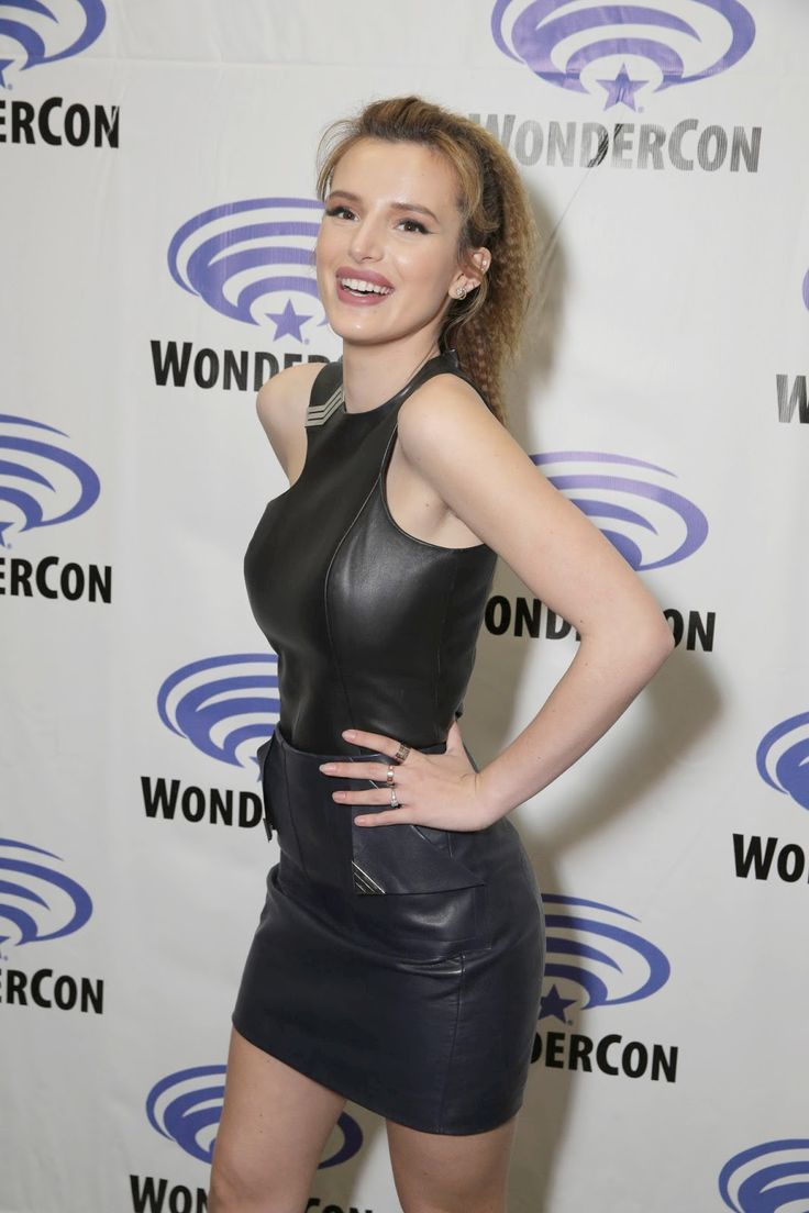 American actress Bella Thorne wearing a black leather top and dark blue leather mini-skirt: