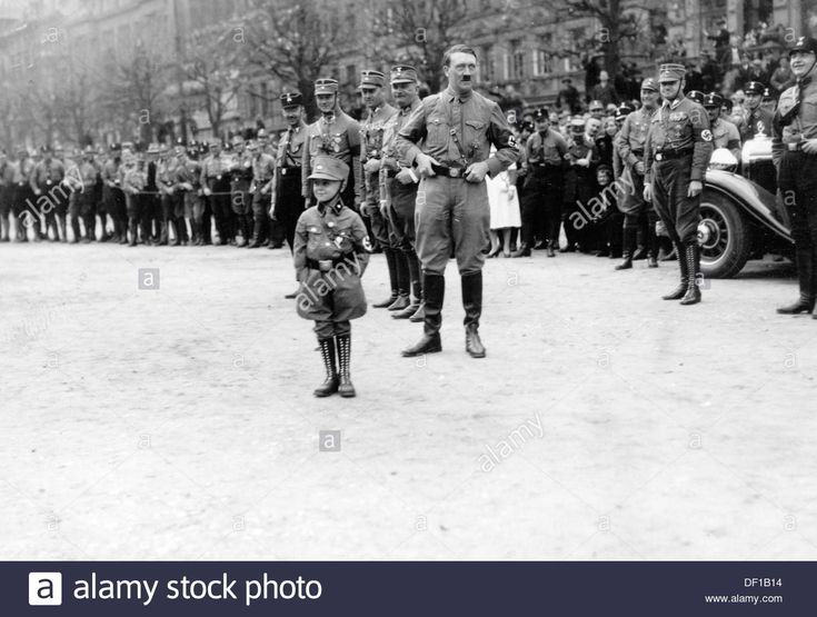 A small boy in SA uniform with swastika armband is pictured in front of Adolf Hitler during the march of the SA in Braunschweig, Germany, on 17/18 October 1931. Photo: Berliner Verlag/Archiv Stock Photo