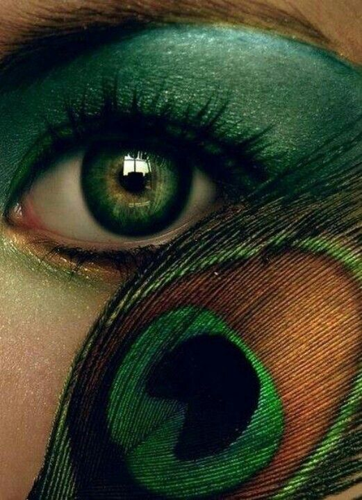 Beautiful artwork, green eyes, make-up and a feather.
