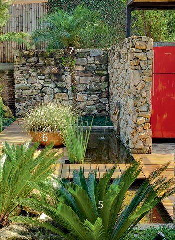 Um muro de pedras moledo marca o início do espelho d'água, que é cortado por um deque de madeira de demolição. Para esse trecho, Flavia escolheu cicas (5), íris e barba-de-serpente (6). Atrás da palmeira-fênix (7), um cercado de bambu garante privacidade