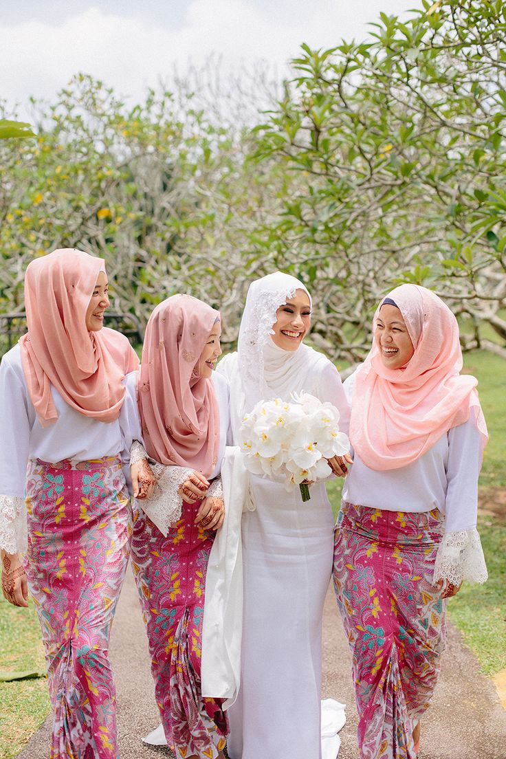 Bride in all white traditional Malay costume from Adila Long and bridesmaids in white Fashion Valet tops, colourful batik skirts from Hello Prints & Patterns and soft pink hijabs // Razif and Sarah decided to celebrate their Singapore wedding solemnisation, or nikah, at Ba'alwie Mosque in a meaningful and intimate ceremony captured by Zakaria Zainal of We Made These.