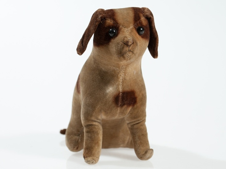 This early model from the traditional Steiff factory shows a seated, unmovable fox terrier made of beige velvet with brown spotted fur, floppy ears, original shoe button eyes, delicate mouth- and nose thread decoration and a short curved tail. He is filled with Kapok. The gorgeous dog has possibly been used as a pin cushion. OUCH! $1587