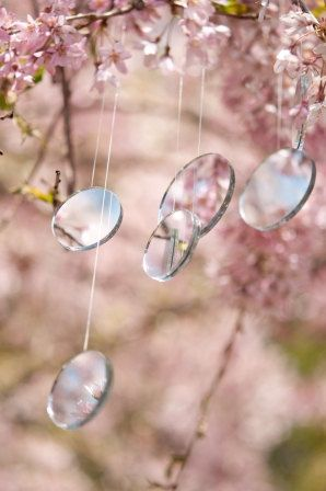 Fairy Lights. Six strands of double sided mirrors, four 11/2 inches in diameter and two 2 inches in diameter, are attached on varying lengths of monofilament line. Hang at uneven lengths over tree branches. The mirrors gently blow in the breeze, reflecting light when the sunlight catches them