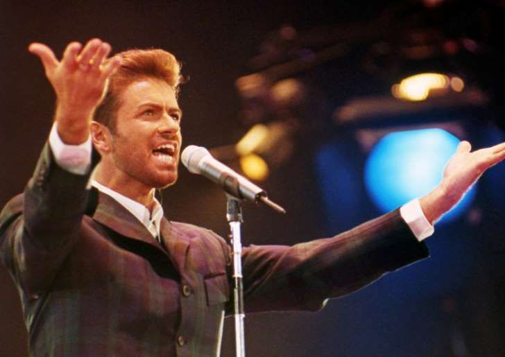 """FILE - In this Dec. 2, 1993 file photo, George Michael performs at """"Concert of Hope"""" to mark World AIDS Day at London's Wembley Arena. According to a publicist on Sunday, Dec. 25, 2016, the singer has died at the age of 53. (AP Photo/Gill Allen)"""