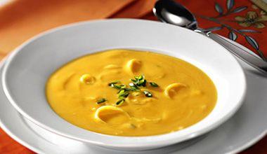 Sopa cremosa de abóbora servida com refogado de alho-poró.