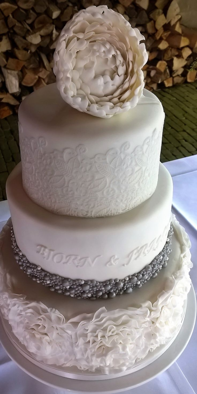 Bruidstaart met ruffles en een pioen.