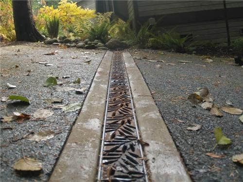 A trench drain with a decorative grate can become a beautiful part of a driveway's design. Iron Age Designs in Burien, WA.