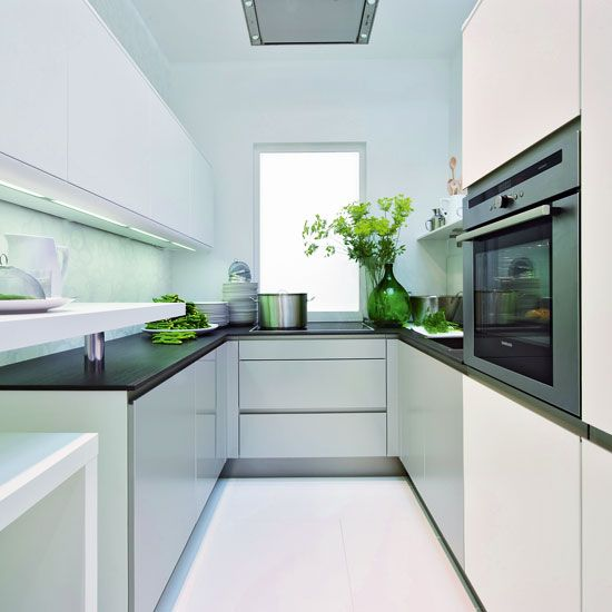 Small kitchen with white cabinetry, black worktops, green glass vase and white flooring
