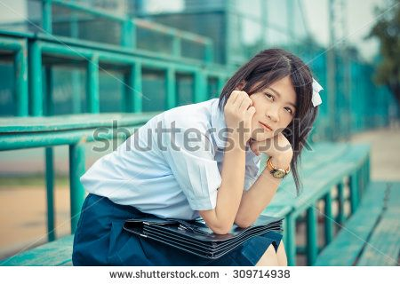 Shy Asian Thai schoolgirl student in high school uniform education fashion is sitting on a metal stand and showing facial bashful expression in vintage color style