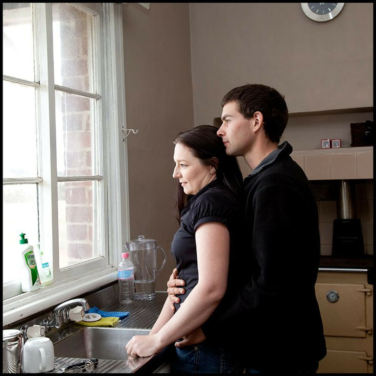 A couples shot in a typically domestic situation - at the sink, looking out the kitchen window of the farmhouse.
