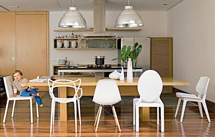 A mesa de jantar espaçosa, com oito lugares, só foi possível porque a cozinha é totalmente integrada com o living. Cadeiras diferentes dão mais graça ao móvel de madeira clara. Projeto de Vanessa Féres