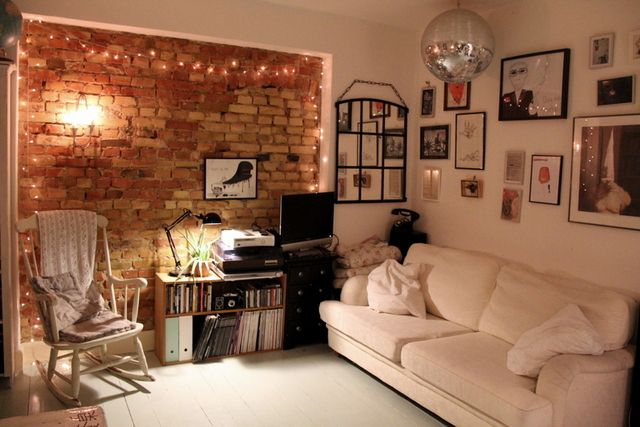 Cosy living room/ lounge. White floor and sofa, one brick wall with fairy lights