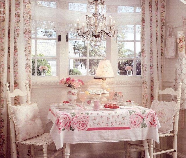Table for two.  Pink and white cottage shabby table setting with vintage table cloth crystal chandelier and soft floral fabrics.  romantic