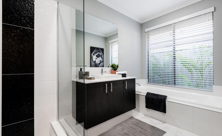 Stylish main bathroom with Caesarstone benchtops, semi-inset vanity basin, mixer tap and glass semi-frameless pivot screen doors