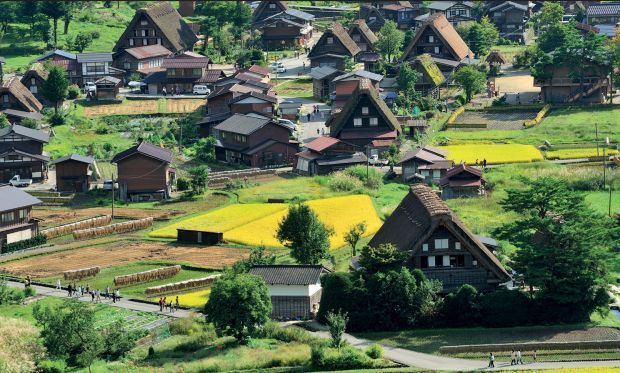 """SHIRAKAWA-GŌ GIFU, HONSHU, JAPAN Shirakawa-gō is one of Japan's most traditional rural villages, clustered at the base of steep, forested mountains in the valley of the Shō River. The village is renowned for houses built in the distinctive slant-roofed gasshō-zukuri (""""praying hands"""") architectural style, which allows them to shed the region's heavy snowfall."""