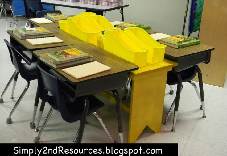 this teacher has small bins for each student, set on a smaller custom made bench/table in between the desks!
