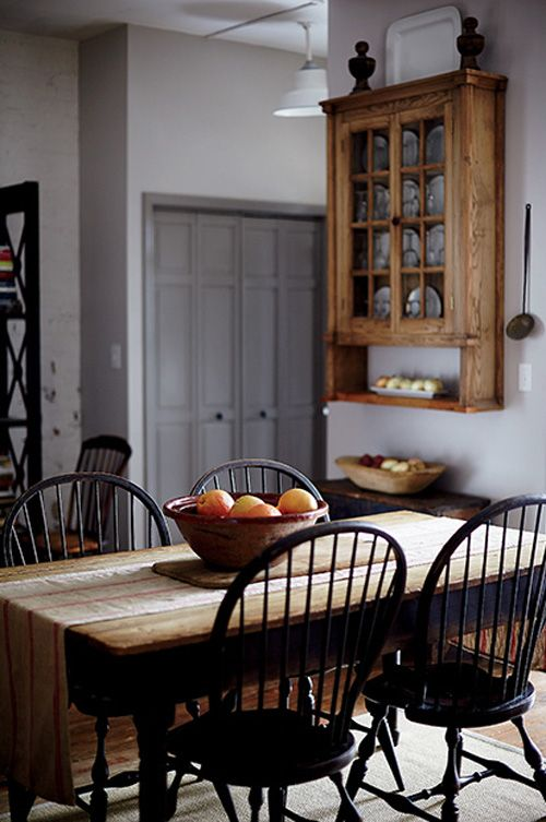 A weathered warehouse. Farmhouse table with natural linen runner and windsor chairs.