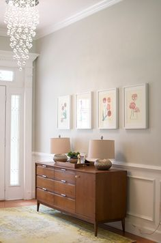 Entry Way with picture frame molding, Benjamin Moore Gray Owl, Mid Century dresser, and fancy chandelier.