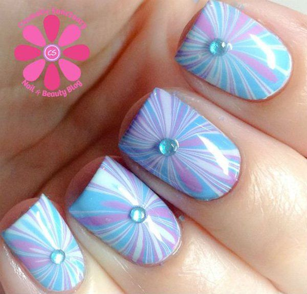 A very cute and striking water marble nil art using white and periwinkle polish atop a baby blue base coat and clear beads.