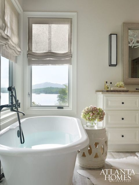 Lake Chatuge reveals its beauty in the master bath, where a freestanding tub, oversize hide rug and linen nailhead mirror contribute to the relaxed but luxurious vibe. Victoria + Albert tub, Renaissance Tile and Bath. Mirror, Max & Company. Hide rug, Huff Harrington Home.