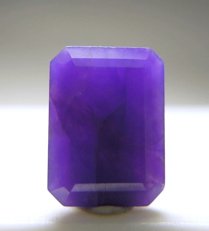 """A bright purple emerald cut Gel Sugilite. The name """"Gel"""" is given to the translucent material that has good   crystallization and gives the finished gem a glassy look. It is rare and very prized. Less than 1% of the mined Sugilite is """"gel"""".   This piece weighs 1.10 carat is well cut with good polish and has lighter purple color veins. From Hotazel.  From Mineral Auctions    via Sabrina Jordan"""