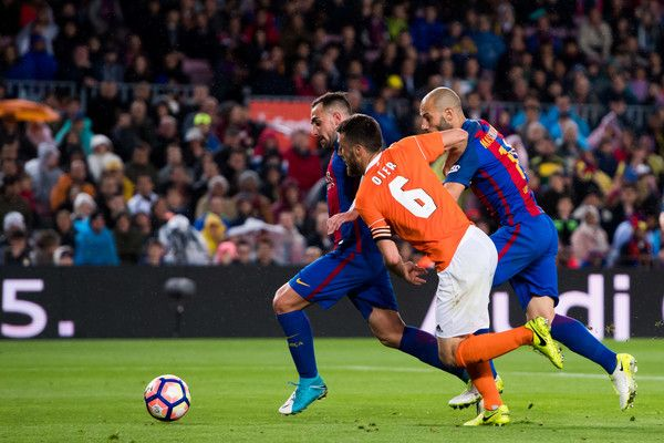 Paco Alcacer of FC Barcelona scores his team's fifth goal under pressure from Oier Sanjurjo of CA Osasuna during the La Liga match between FC Barcelona and CA Osasuna at Camp Nou stadium on April 26, 2017 in Barcelona, Catalonia.