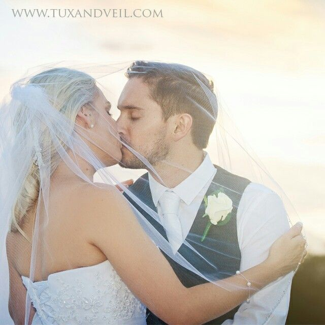 Kissing underneath veil so stunning. Sunset bride and groom. Wedding photo at sunset