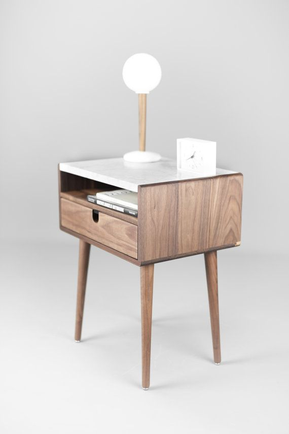 The classic design of our walnut nightstand reflects mid century modern with its clean lines and tapered legs. Its double-tier design has an open cubby space on top for books, with a bottom drawer with carved round-out for a hardware-less look. Completely handcrafted from Class A American walnut selected from only the finest timbers. Legs come in your choice of oak in black or walnut. Beautiful craftsmanship and superior joinery means this is a piece that will last. Made to order, it will…