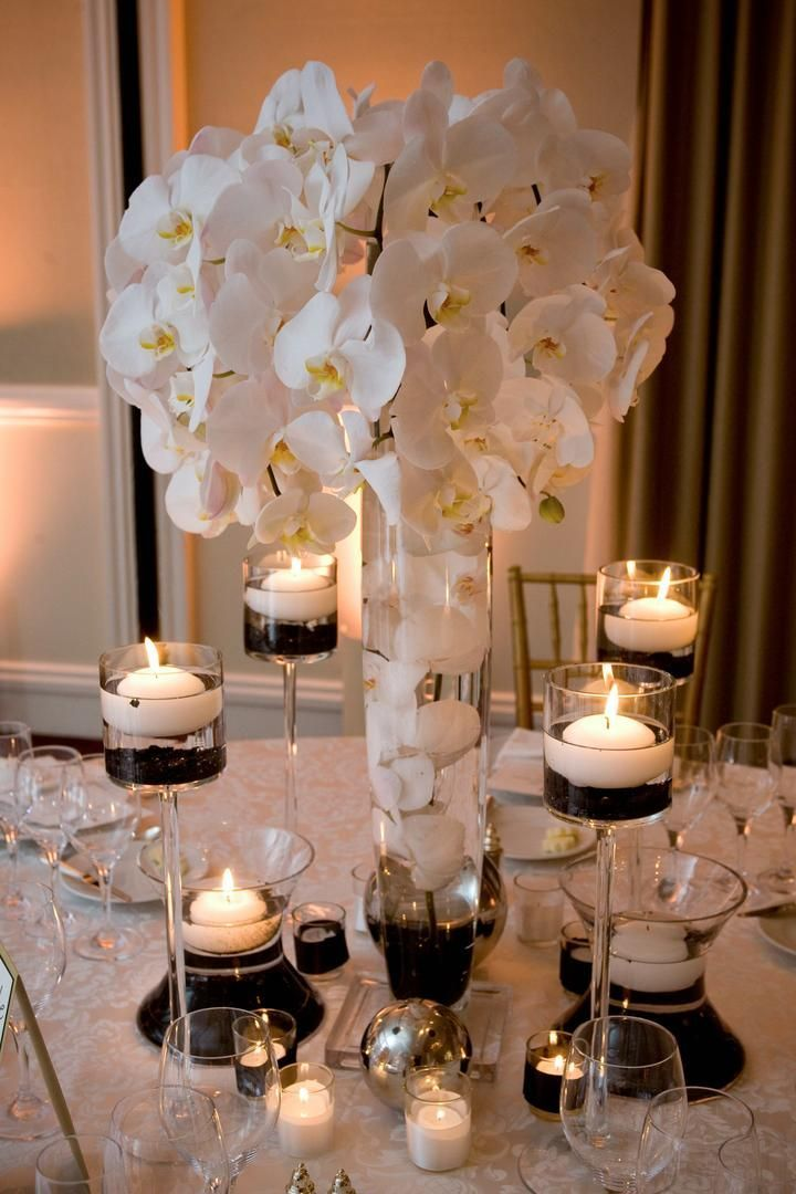 Tall centerpieces composed of white orchids were surrounded by candleholders filled with black sand and floating candles. #SubmergedFlowers Photography: Lawrence Crandall Photography. Read More: http://www.insideweddings.com/weddings/white-black-gold-oceanside-wedding-in-california/309/