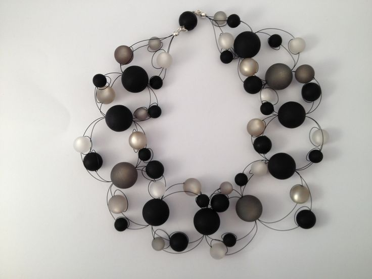 Samtig glänzende Perlen umspielen Hals und Dekolté und scheinen zu schweben. Die Farben schwarz, weiß und grau machen diese Kette zu einem puren De...