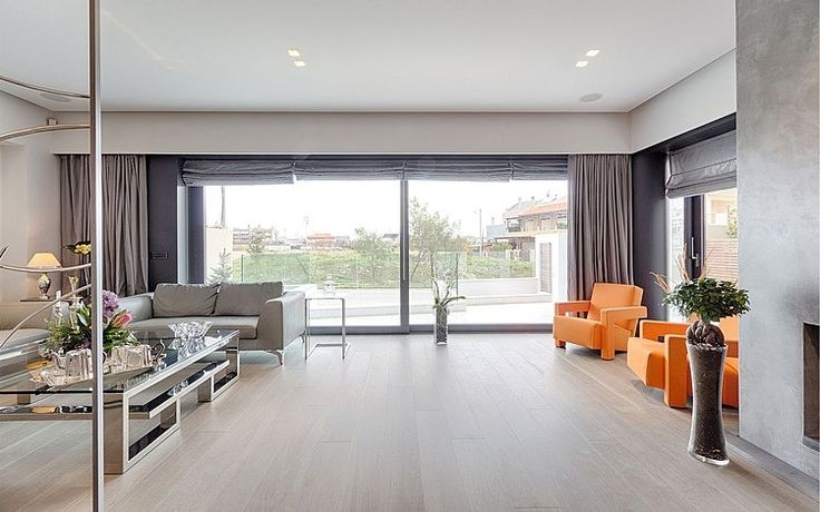 House in Gerakas by Office Twentyfive Architects - orange lounge chairs