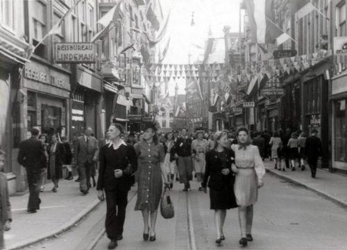 Bevrijdingsdag. Mensen lopen arm in arm door de met vlaggen en slingers versierde  Barteljorisstraat, na de bevrijding van Haarlem, Nederland  mei 1945.
