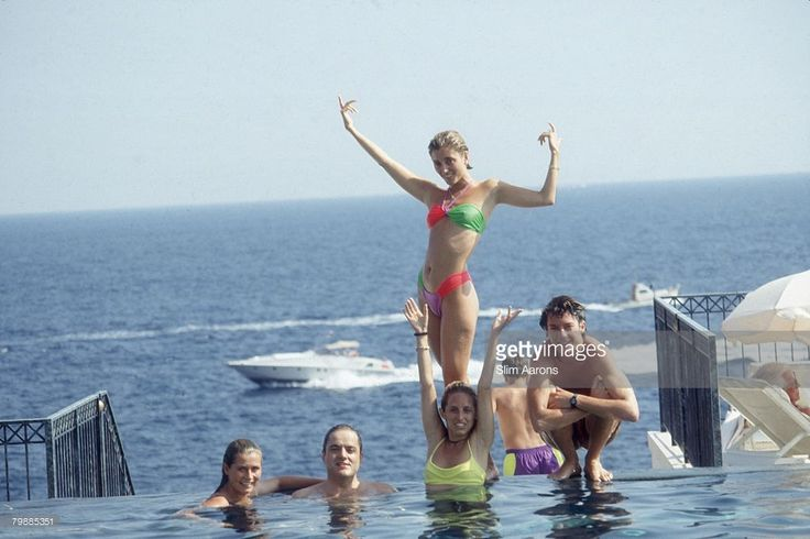 Marie Chantal Miller, future wife of Prince Pavlos of Greece, strikes an extravagant pose above her sister Pia (in yellow), who is soon to marry Christopher Getty. They are lounging in the pool of the Hotel Belair, Cap Ferrat, July 1991.