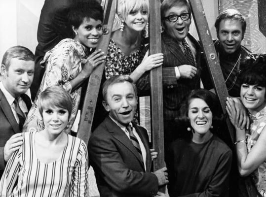 """The """"Laugh-In'' cast: (bottom) Dave Madden, Judy Carne, Henry Gibson, Ruth Buzzi, Jo Ann Worley; (on ladder) Chelsea Brown, Goldie Hawn, Arte Johnson, and Alan Sues. (Nbc File)"""