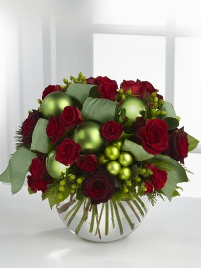 A christmas centerpiece with red flowers and green