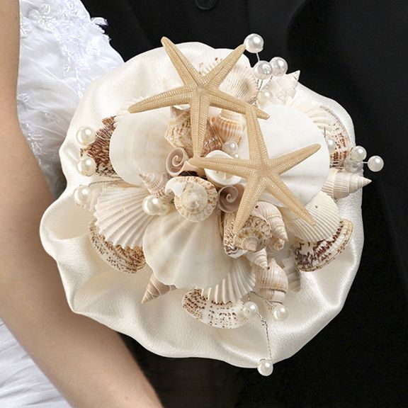 """Coastal Seashell Bouquet - For beach themed and destination weddings, this seashell bouquet makes a great accessory for the bride to hold. The clear acrylic handle holds a bouquet made of an ivory satin ruffle and a collection of different seashells and starfish. Size: Width 6"""". Length 6.5""""."""
