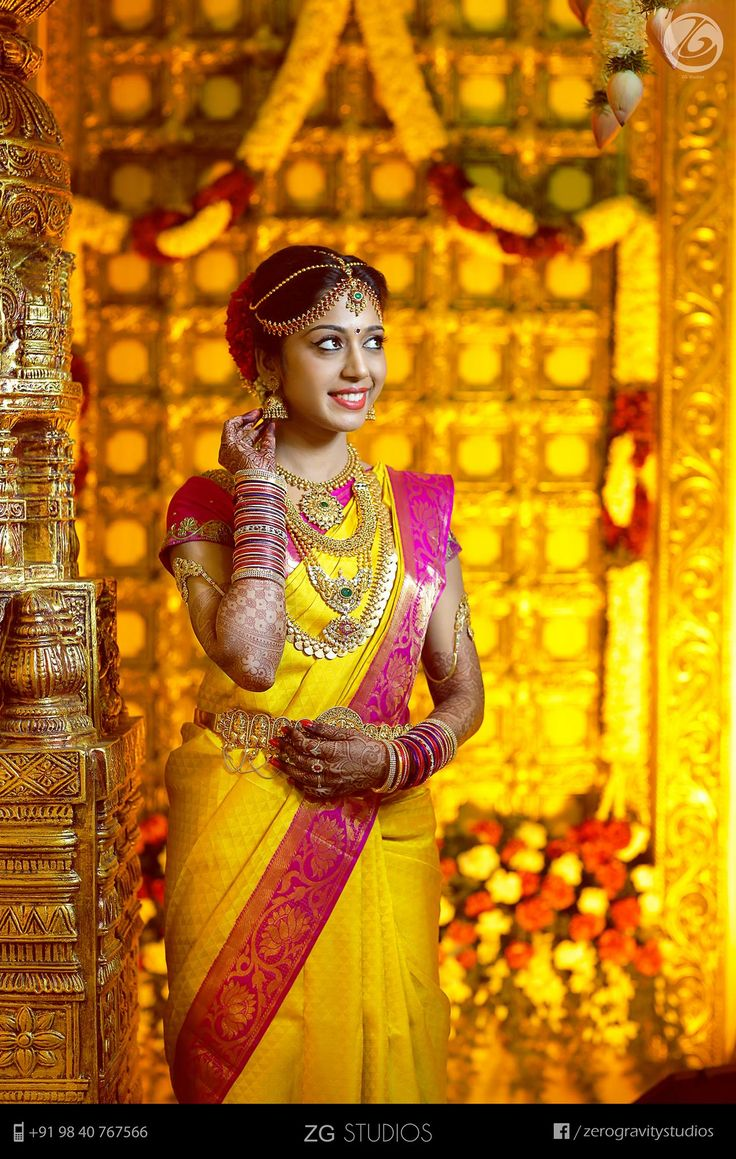 South Indian bride.  Gold Indian bridal jewelry.Temple jewelry. Jhumkis.Yellow and pink silk kanchipuram sari.Braid with fresh flowers. Tamil bride. Telugu bride. Kannada bride. Hindu bride. Malayalee bride.Kerala bride.South Indian wedding.