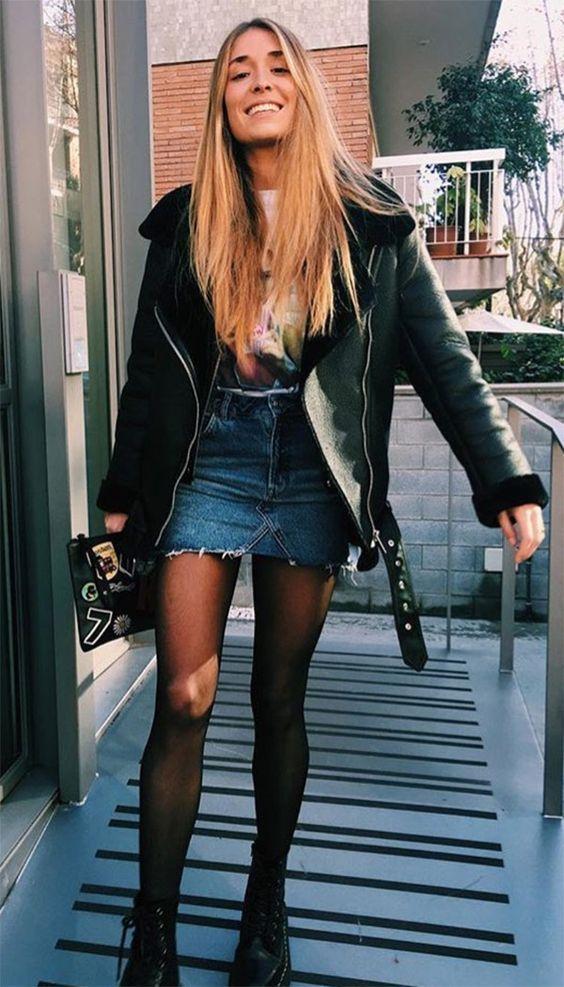 Jaqueta de couro, t-shirt estampada, saia jeans, meia calça preta, coturno preto