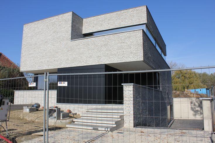Knappe vormtaal, leuke combinatie van baksteen en gevelpanelen (Trespa-plaatwerk), garage in de kelderverdieping. Door Dirk Nijsten.