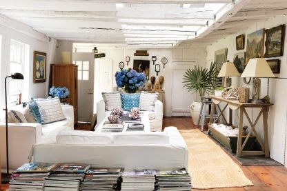 "House tour: the idyllic Hamptons cottage of two antique dealers: The only thing Mead didn't touch with a wash of white were the original 18th-century floorboards. ""I wanted them to stay like that forever to remind us of the house's 1740 former self,"" he says. Touches of blue from fresh hydrangeas and dyed French linen cushions stand out against the all-white backdrop."