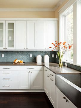 blue backsplash tile is nice contrast to neutral background of white cabinets and dark counter