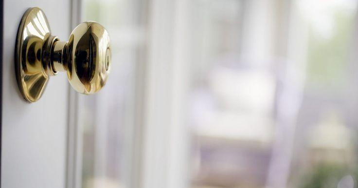 Cómo desmontar un pomo que se engancha a la puerta. Una puerta en una zona de alto tráfico, tal como un dormitorio o cuarto de baño, puede ser abierta y cerrada varias veces al día. Este uso constante puede desgastar el mecanismo interior del pomo de la puerta, haciendo que el seguro de la puerta no se libere al girar el pomo o falle al engancharse al cerrar la puerta. La sustitución del pomo de la ...