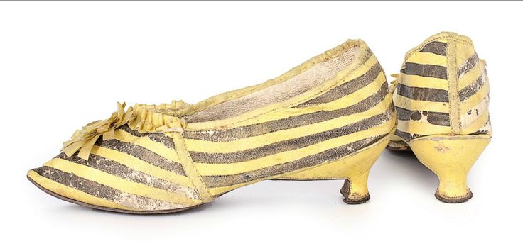 A pair of yellow and black striped leather shoes, 1790s, with pointed toes, low yellow Italian heels, trimmed with yellow rosettes and ribbons. 28cm/11 inches long. From Kerry Taylor Auctions, Passion for Fashion and Textiles auction catalog, November 20, 2017.