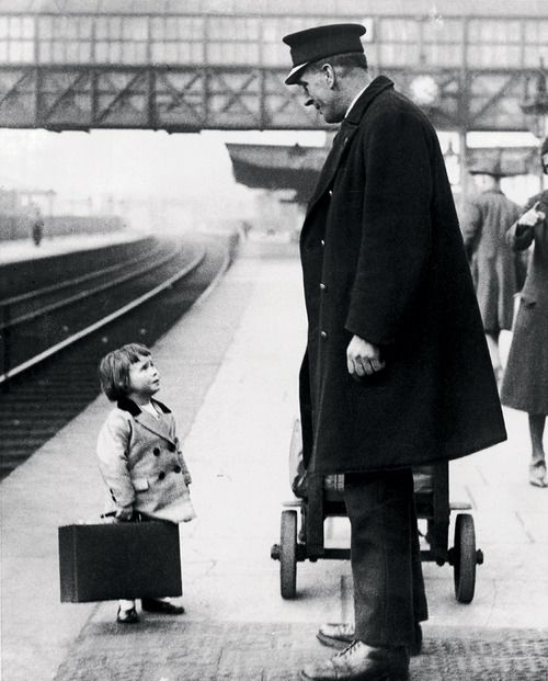 A young passenger asks a station attendant for directions. Bristol Railway Station, England, 1936,