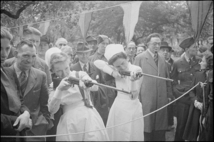 War Fair: Holidays at Home at a fete in Russell Square, London, 1943. Two nurses have a go at a shooting game at a fair in Russell Square. The aim is to shoot cigarette packets with corks. A large group of people, including RAF and Army personnel, watches them as they fire. Bunting decorates the square behind them.