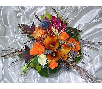 Fall bridesmaid-miniature calla lilies, protea, gloriosa lilies, thistle, roses, monbretia pods, and eucalyptus. Original Design By Fireside Flowers.