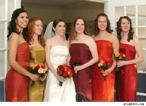 Mismatched bridesmaids in red, orange, and yellow dresses.