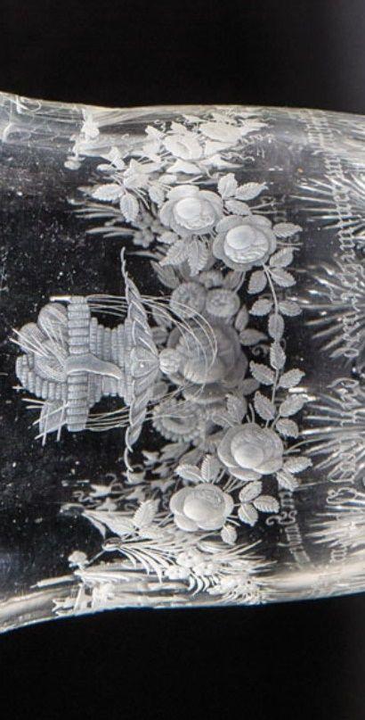 Detail - Nordböhmen, Anton Simm, Gablonz zugeschrieben, um 1835  Fußbecher mit Lob der Hausfrauen  Farbloses, partiell mit verschiedenen Schliffdekoren verziertes Glas. Auf der glockenförmigen Wandung fein geschnittene, teils polierte Attribute für Handarbeit, Küche und Zierde einer Hausfrau, darunter Inschrift ''Sie regen ohne Ende die fleißigen Hände und fügen zum Guten den Glanz und den Schimmer und ruhen nimmer''. H. 11,8 cm