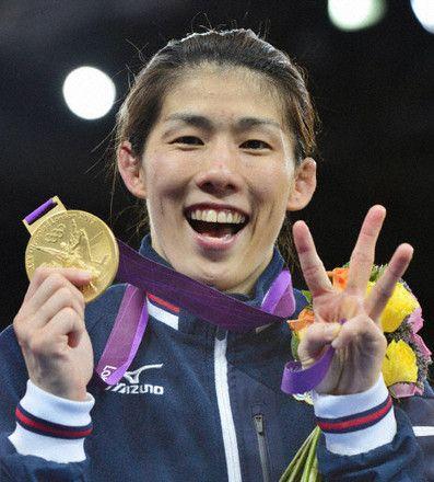 女子55キロ級で3連覇を果たし、メダルを手に喜ぶ吉田沙保里=エクセル(共同)